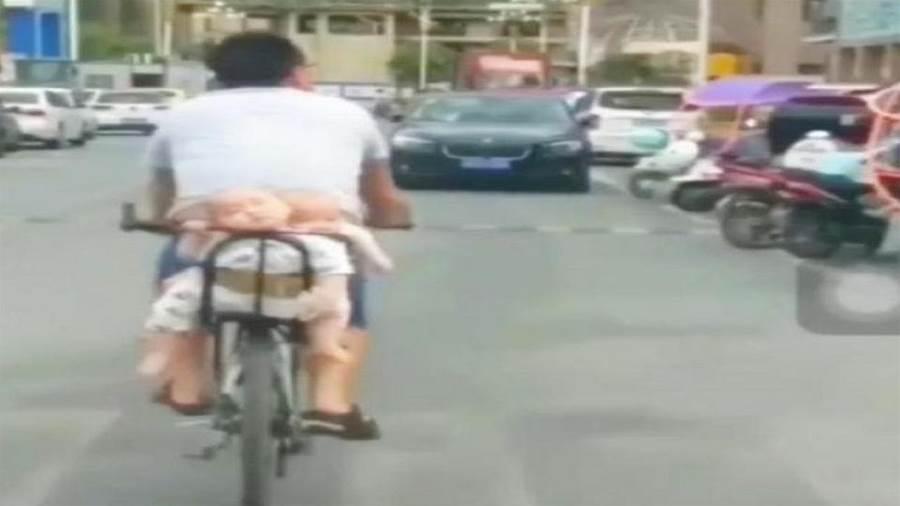 雙胞胎坐爸爸自行車後座,悠然地睡著了,這爸爸心真大